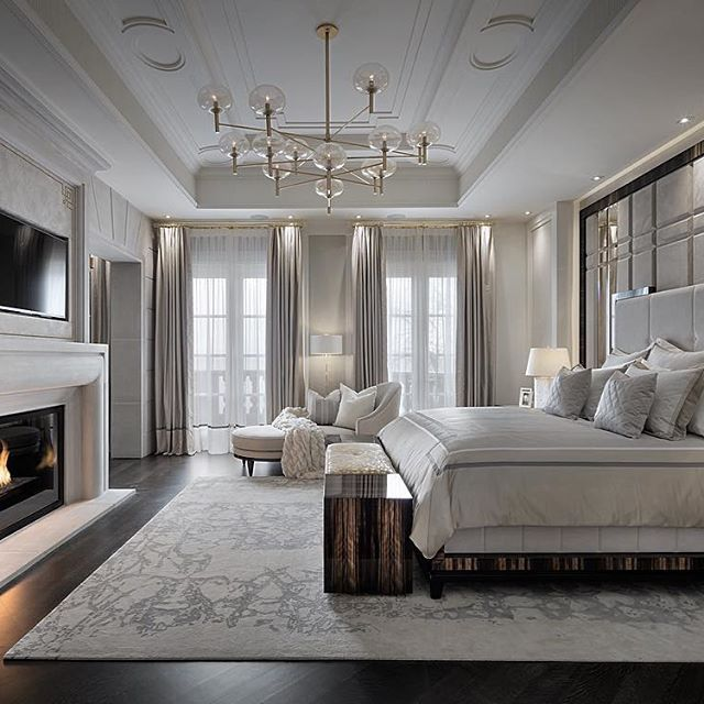 Bedroom design, upholstered headboard, white color palette, stone fireplace, area rug, modern lighting.