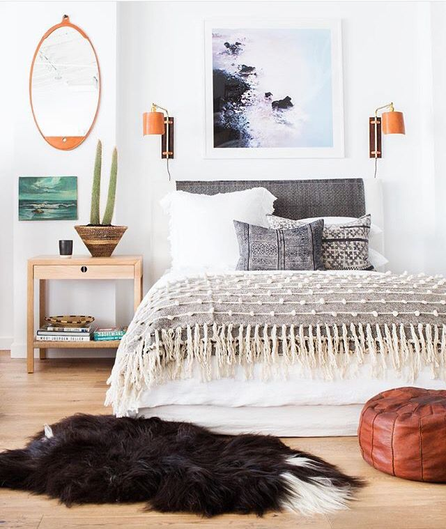 Bohemian Bedroom with grays, blues, creams, white and brown. Potted plant, light washed wood night stand, fringe throw, oval mirror and leather pouf