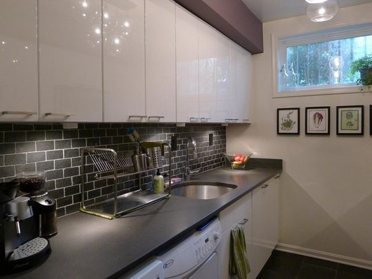 small kitchen with slate floors cabinets and back splash are neat -- even has laundry spots