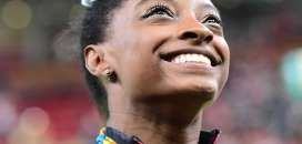 Simone Biles was all smiles as she made gymnastics history with an easy victory in the all-around co... - EMMANUEL DUNAND, Staff