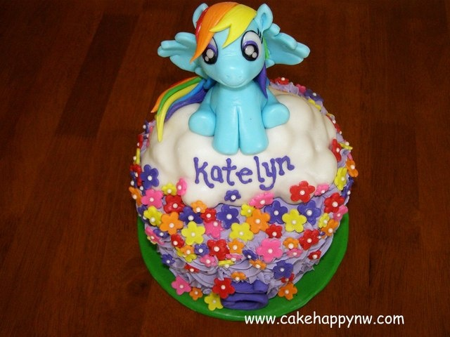 My Little Pony themed birthday cake for a little girl's 5th birthday!  Rainbow Dash and all decorations are made of fondant, gumpaste and royal icing.  www.cakehappynw.com