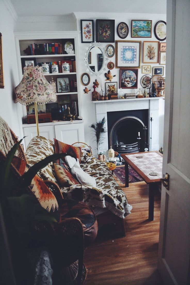 Excellent display of prints and knick knacks  above the fireplace. And I am in love with the granny style floral floor lamp.
