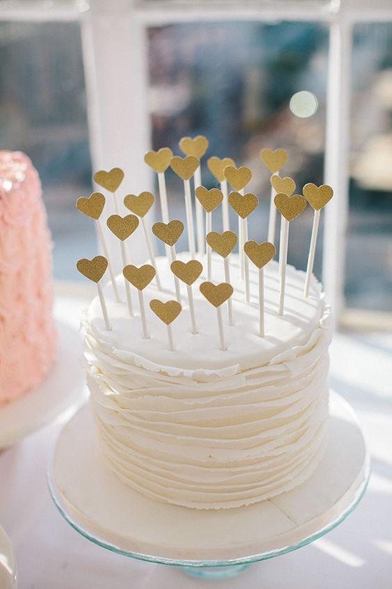 Topo de bolo de coraçõezinhos de glitter em palito de madeira. Foto: 100 Layer Cake.