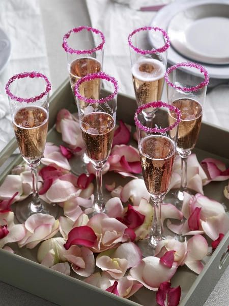 What a beautiful way to serve drinks. Colored sugar on the rims & rose petals around the bases!