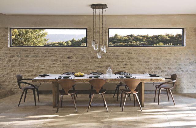 Jouxtant la cuisine et ouvrant largement sur la campagne provençale, la salle à manger campe son style autour d'une table en bois brut. Plus de photos sur Côté Maison http://bit.ly/1T5V6vk