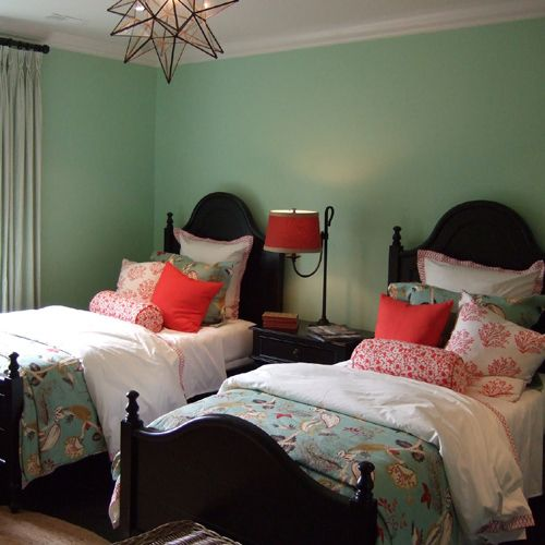 A color scheme can completely transform a room – here, this fun kid's bedroom for two is drenched in a calming shade of mint green with lovely flecks of hot pink.