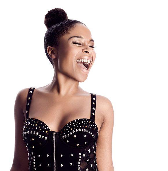 Nabiha Bensouda wearing a black studded top with her hair in a bun singing