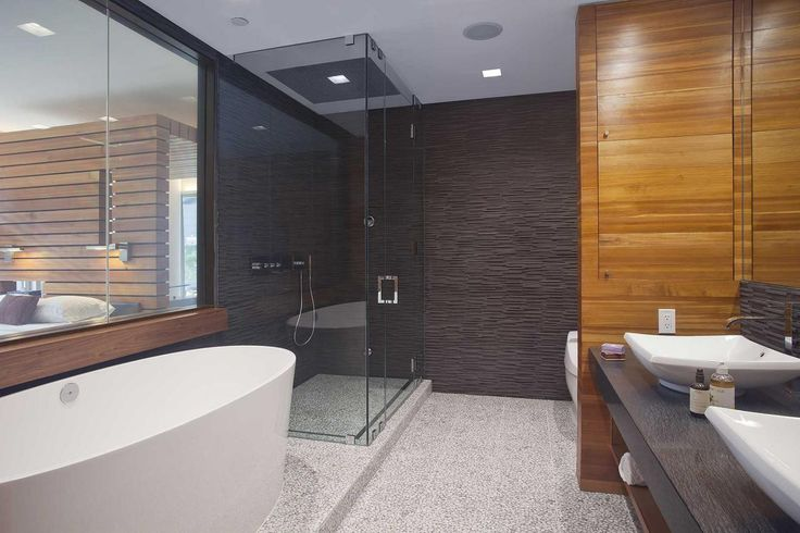 This luxurious modern bathroom features a cool mix of textures: pebbled floor, wood paneling and an all-glass shower. The freestanding soaking tub ups the ahhh-factor.