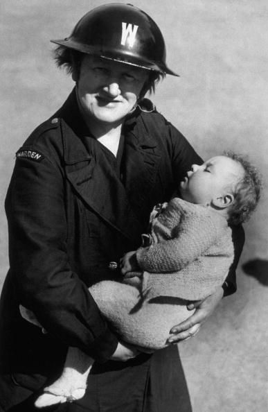 1942: An air raid warden cradles a homeless child in her arms, following the recent Baedeker raid on Norwich. (Photo by Keystone/Getty Images)