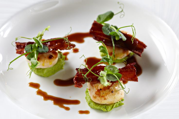 Starter of pan seared scallops, bacon, pea-puree, micro green garnish with redux drizzle