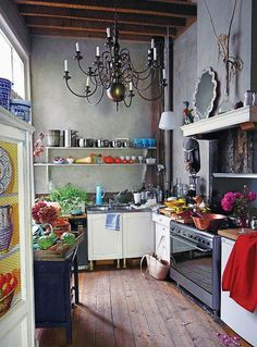 An Artists Kitchen. D'You really need to change your kitchen & spend a fortune? Notice how the cheap kitchen units (no offence) are unnoticeable& transformed by the beauty of stunning one off items such as the chandelier, unfitted table, mirror & the decorative power of fruit, vegetables, & flowers that animate the room.