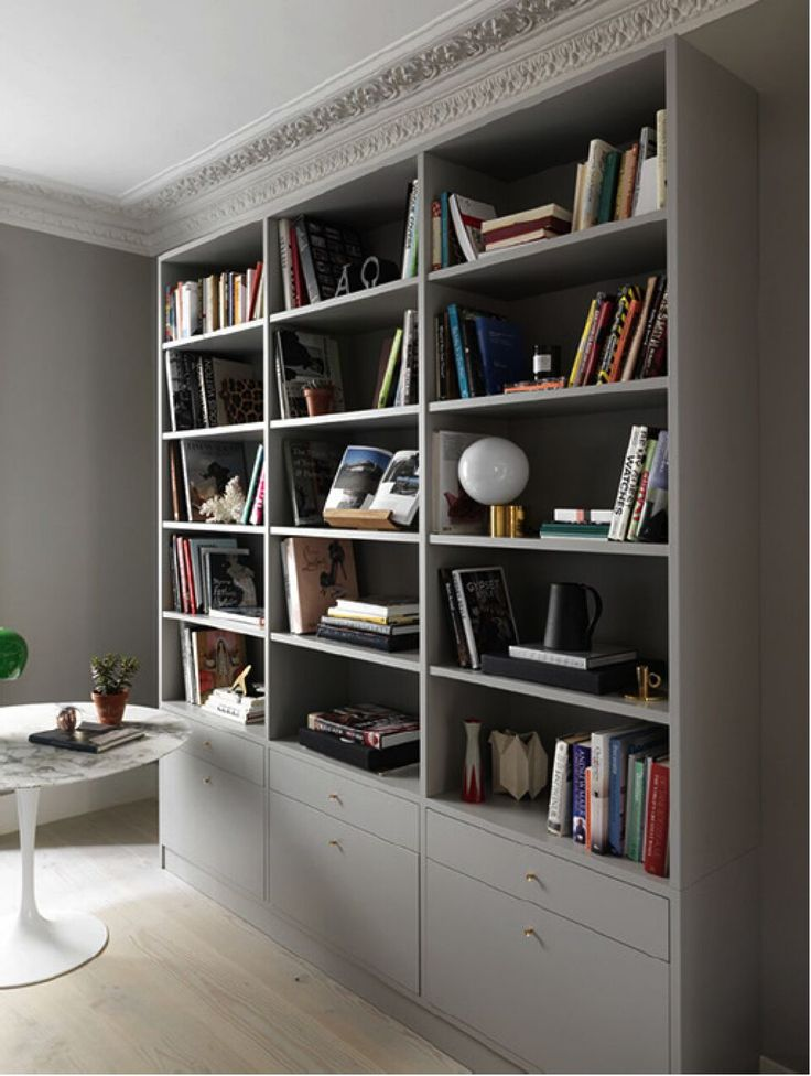 Custom bookcase and saarinen table (that conceals technology wires) in a Notting Hill town house by interior designer Charles Mellersh   Remodelista