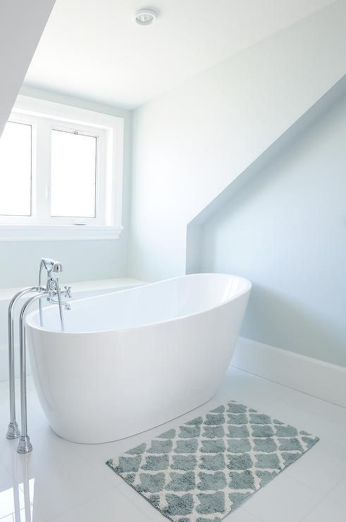 White and blue bathroom with blue bath mat placed in front of an oval freestanding tub and a ...