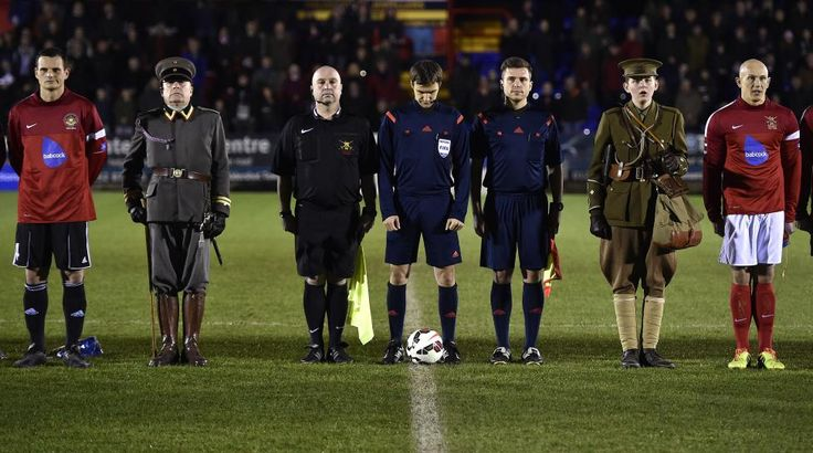 British Army soccer team captain Sergeant Keith Emmerson (R) and his German counterpart, Bundeswehr captain Alfred Hess (L), stand with match officials and mascots wearing World War I uniforms at Aldershot Town FC stadium in Aldershot in south England, December 17, 2014. The two teams were playing each other in a 'Game of Truce' soccer match, commemorating 100 years since the famous peaceful interlude to fighting in World War