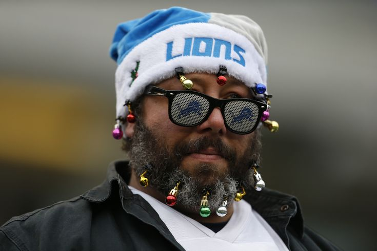 Did the Christmas tree fall into this Detroit Lions fan, or did he fall into it? (AP/Landers)