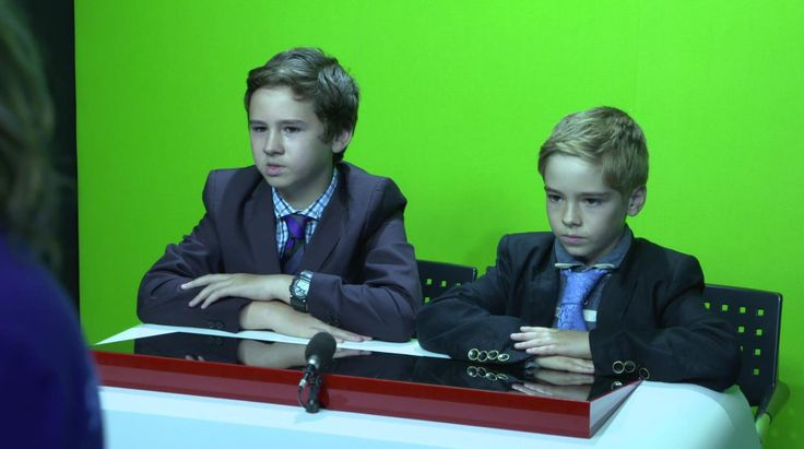 Two serious young news anchors at Sky Academy!