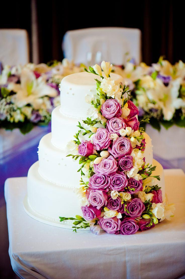 Čtyřpatrový svatební dort, potažený bílým fondánem a dozdoben živými květy.