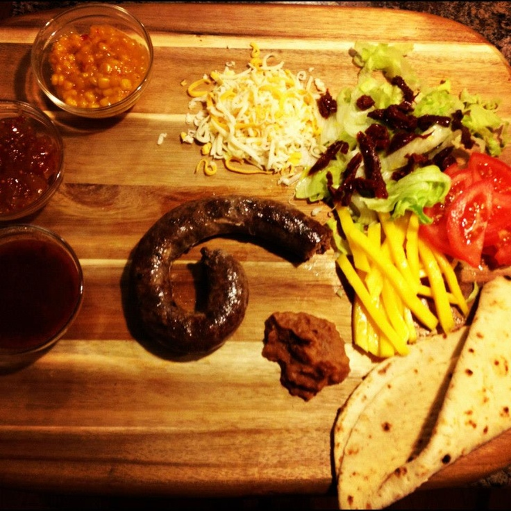 Bokkie's Boerrito  Ingedients:   Boerewors  fresh tomato  ice berg lettuce  Sundried tomatoes  Mango  Refried beans  Chipotle Salsa  Corn relish  Onion relish  Grated havarti and cheddar cheese  tortilla