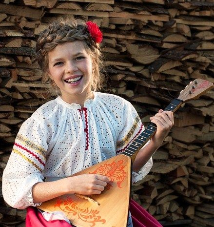 Russian girl playing balalaika (Russian string instrument) in traditional clothes. Three strings tuned A E E