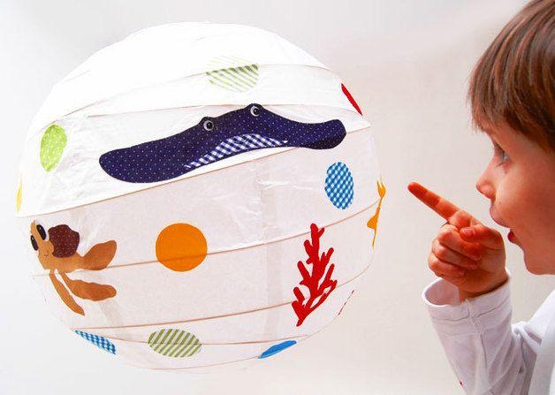 Zauberhafte Papierballonlampe mit Unterwassermotiven für das Kinderzimmer. Die Stoffmotive wurden alle liebevoll mit der Hand ausgeschnitten und einzeln auf den Ballon geklebt. Die Lampe wirft ein...