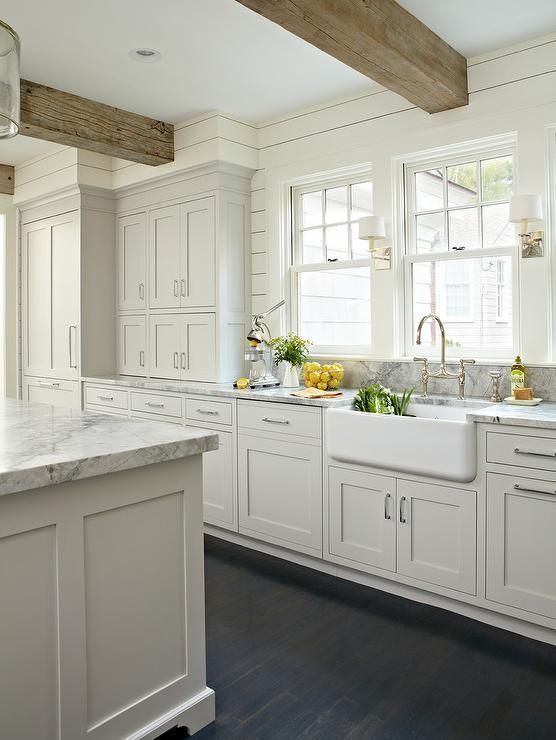 Light gray and white kitchen with a classic design features stacked light gray shaker cabinets accented with nickel pulls and fitted with Super White Quartzite countertops holding a farmhouse sink and polished nickel, deck bridge mount, gooseneck faucet under single hung windows separated by small sconces mounted to ivory shiplap walls supporting rustic wood ceiling beams hung over dark stained oak wood floors.