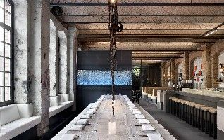 Sage Restaurant, Berlin -- Retrofit -- large, hanseatic appearing brick building was once a silk mill, later a coffee roastery. The generous dining area impressed by modern design and artistic space and lighting design.