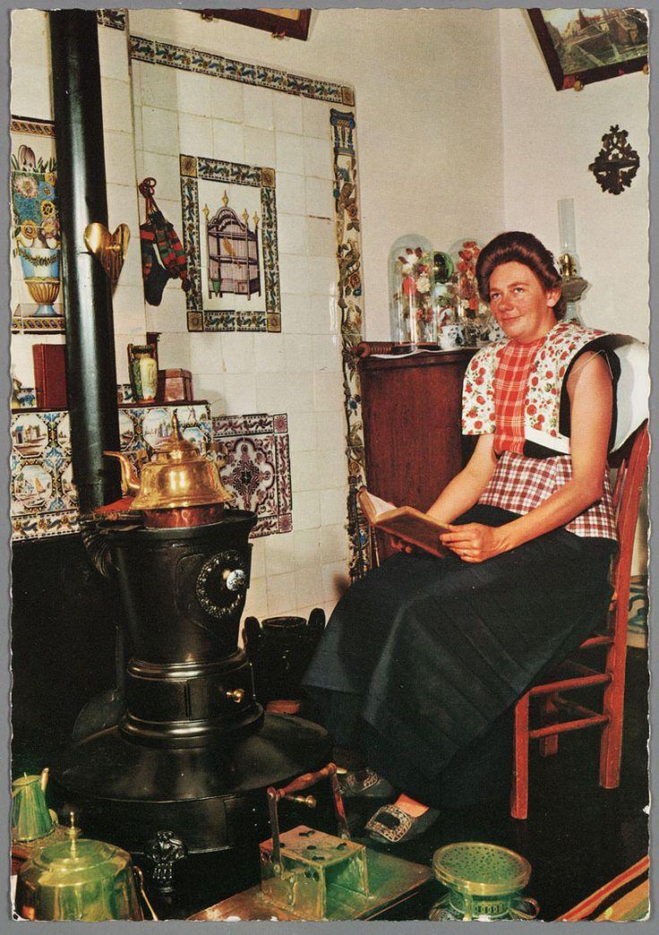 Spakenburg In de Korporaal Moderne vrouw in traditioneel interieur. 1970-1990 Poserende vrouw in moderne zomerdracht. Onder de wit gebloemde kraplap met de gedeelde rode doek draagt zij een mouwloos truitje, zonder boormouwtjes. Op het schort een rood geruit stukje. Voor de foto heeft zij schoenen met zilveren gespen uit de jaren dertig aangetrokken. Zij zit in een traditioneel interieur (mogelijk een museumopstelling). #Utrecht #Spakenburg