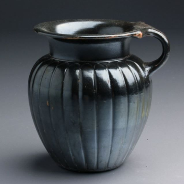 Greek Apulian pottery jug, 4th century B.C. Greek Apulian black glazed pottery jug with ahndle, magnificent iridescence, 9.5 cm high. Private collection