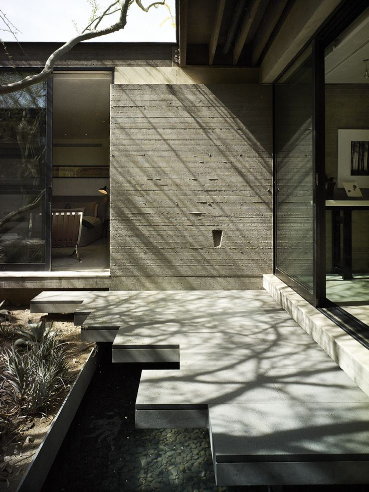 """Board-formed concrete walls create the core of the house and establish its organic feel. """"There's really no other cast-in-place concrete on the street,"""" says Sarah, """"but you don't even see it until you've made it through  the front courtyard."""" There, beneath a deep overhang, the couple designed a jagged pathway cantilevered over a water feature—bringing the sounds of water inside and reflections of light into the sitting area."""