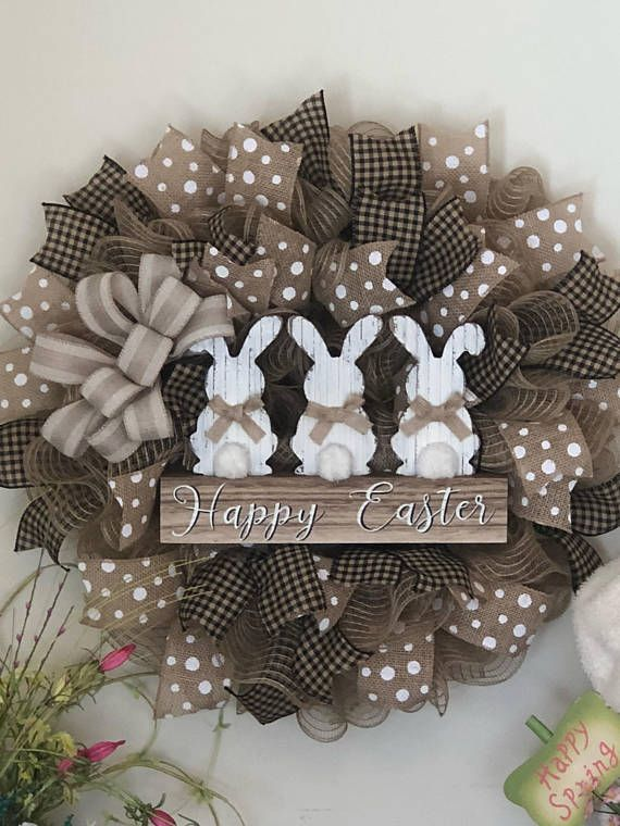Spring is in the air with this wreath! This adorable wreath is done in burlap deco mesh with a houndstooth print and white polka dot print ribbon.Centered with a trio of bunnies. Great farmhouse/country decor! Approx 22 inches