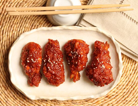 The twice-fried, sweet-spicy chicken is first dipped in a thin flour, corn starch and water batter and fried in canola oil. It is then fried a second time producing a thin, very crisp crust, which is much less greasy then American fried chicken. The wings are then doused in a sauce to die for made with garlic, ginger, soy sauce, gochujang, rice vinegar, sesame oil and honey.  From Cook & Be Merry Website