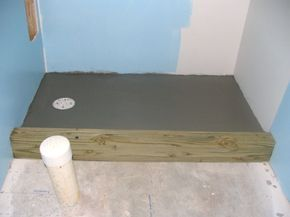 How to Finish a Basement Bathroom - build the tile shower pan. I install the shower curb, mortar bed, shower pan liner and cement backer board on the walls.