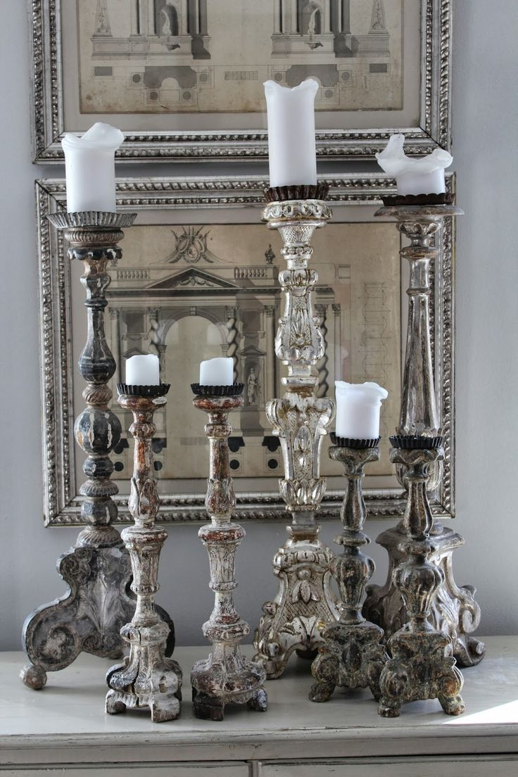 Tall, ornate candleabras in front of architerctural prints - La Maison Gray- Interiors