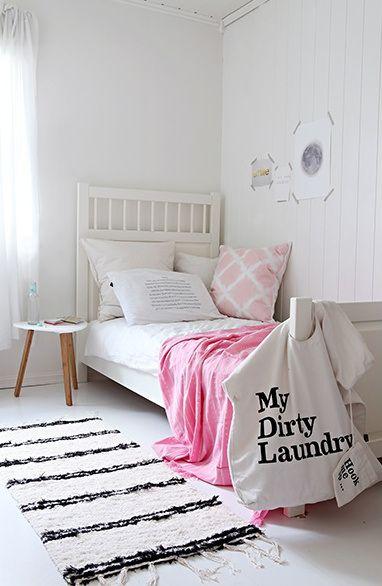 Mooie witte meidenkamer met subtiele roze accessoires.