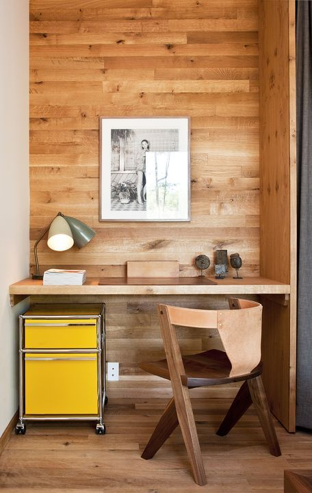 A yellow Pedestal filing cabinet by USM is tucked under a built-in desk in the guest bedroom. The leather-back chair was designed by Mich...