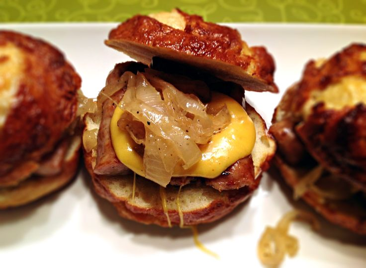 Bratwurst sliders with beer cheese and beer braised onions served on pretzel rolls.