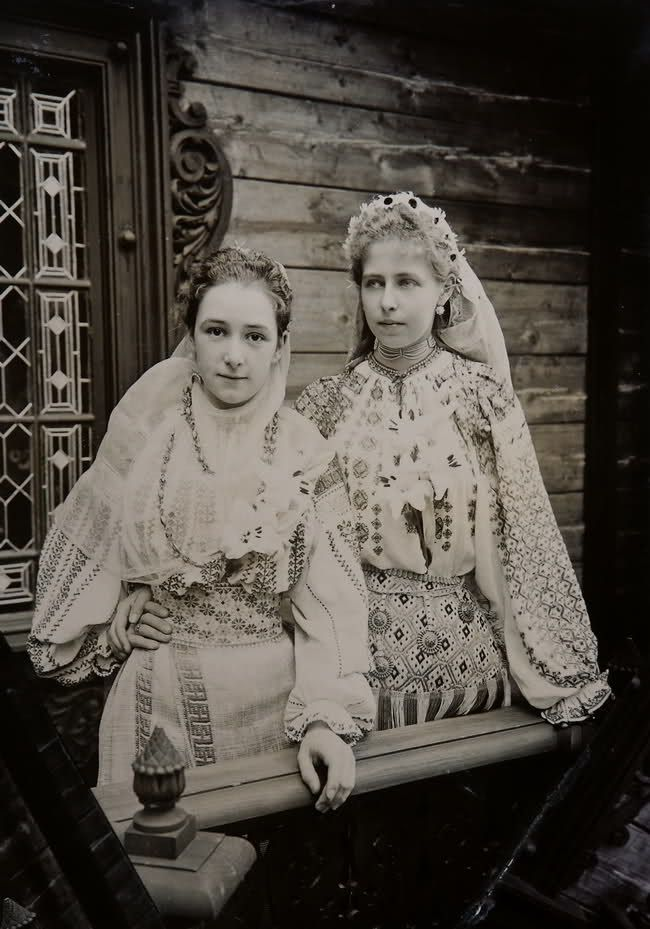 Princess Marie of Romania with lady in waiting (??)  both in typical romanian folk dresses