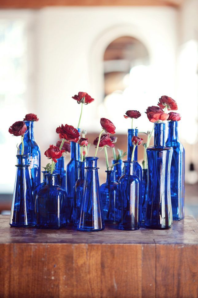 Give your Americana wedding a unique flair with gorgeous blue accents such as these glass bottle arrangements.
