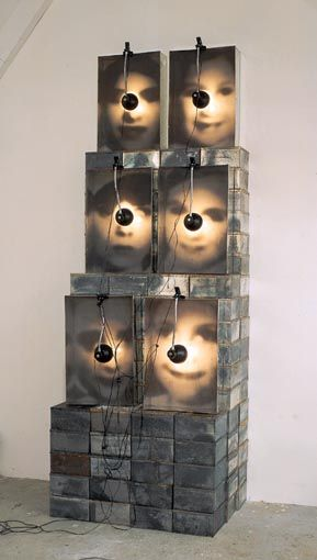 Christian Boltanski Reliquaire, 1989 (La Fête du Pourim) 132 tin boxes 6 metal drawers with black and white photographs, grids and lamps Size of each photo 60 x 40 cm Overall size 271 x 92 x 69 cm