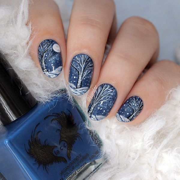 A magical looking winter nails art design. Painted in midnight blue base color, the trees are then painted in black polish and decorated with white polish as the snow and falling snowflakes.