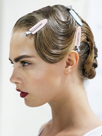 Jason Wu Spring 2013  Odile smoothed Kérastase Elixir Ultime Oléo-Complexe into hair for a glossy, wet texture, then made a deep side part. After sectioning off the hair just before the ear, she sculpted the front portion into a finger wave that added a ladylike element to the look.