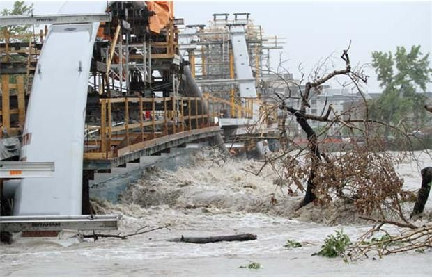 The raging Bow River pushes trees against St. Patrick's Bridge in Calgary, Alberta on June 21, 2013. Photograph by: Leah Hennel, Calgary Herald