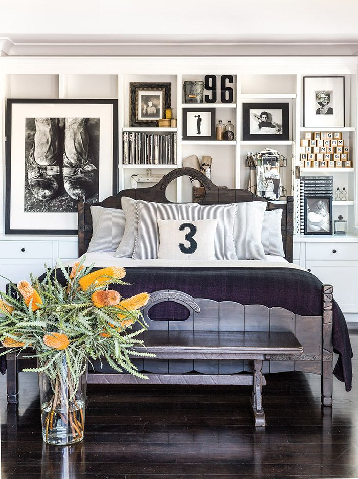 Bedroom with white built-in unit, artwork and books, large plants in a glass vase, white walls, wood bed frame, dark wood floors, and striped bedding