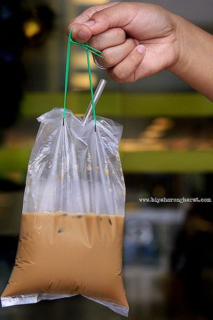 Kopi Ice (Sweet Iced Coffee) | WHAT IT IS: Putting the Frappucino to shame, iced coffee at hawker stalls or traditional coffee shops in Singapore is brewed strong in a metal pot with a long spout, then mixed with sweetened condensed milk, poured over ice, and served in a small drawstring bag with a straw (pictured above). WHY IT'S DELICIOUS: Between the strong brew and the super sweet milk, it's like drinking a thin milkshake with a serious caffeine kick.