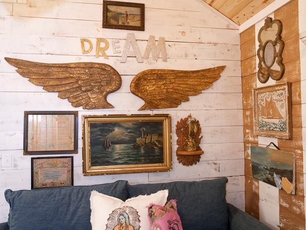 Where do you find wings like these?!?...Decorate With Upcycled Wall Art, Shelves and Storage: A collection of flea market oil paintings are paired with some gold-finish pieces to complement the shabby-chic whitewash walls.  From DIYnetwork.com
