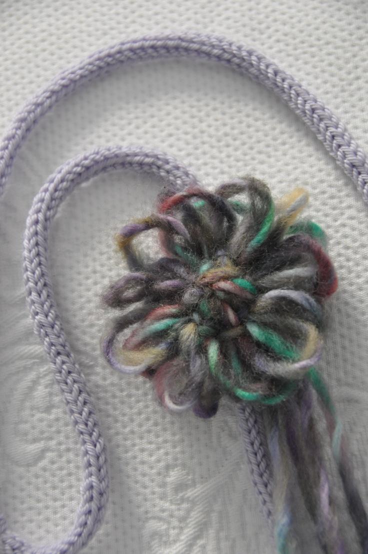 Collana in lana con fiore applicato.