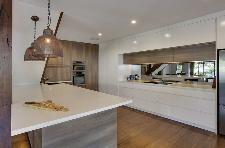 Ultra modern style kitchen: Butlers pantry with Caesarstone bench tops, polyurethane doors and Polytec Sepia Oak Ravine breakfast bar. Matching Overhead Sepia Oak Ravine lift up doors.