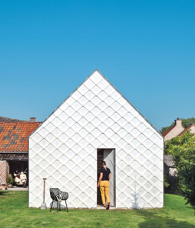 Architect Indra Janda hand-cut sheets of polycarbonate into 15¾-inch square shingles and clad the entire timber structure—a gabled roof a...