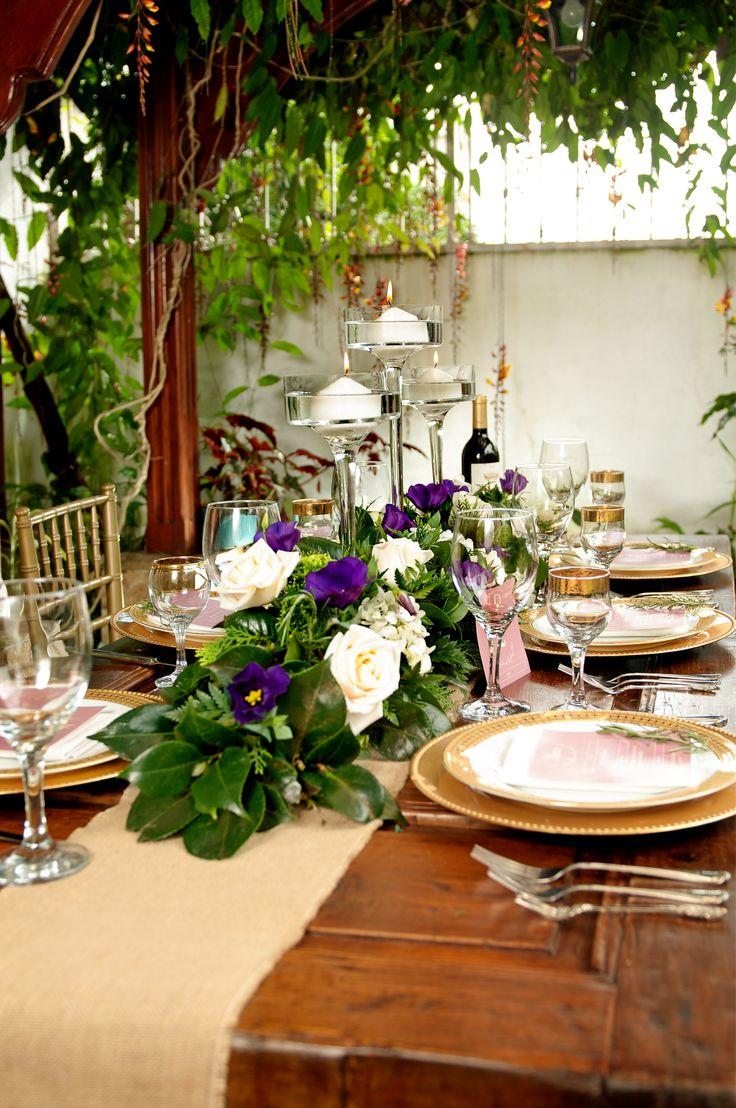 La Combinación de florales en forma lineal utilizando rosas ivory, hortensias en su tono natural, lisianthus morados y una variedad de follajes.