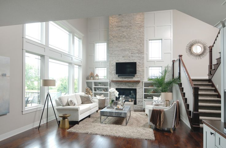 Two-story height great room inspiration with stacked stone fireplace. What a dream living room! Open layout, dark wood floors, built-ins and transitional furniture.